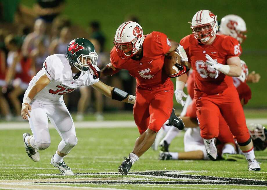 Katy running back Kyle Porter (5) fends off The Woodlands' defensive back David Lee (33) during a high school football game Friday, Sept. 11, 2015 in Katy, Tx. Katy won 14-7.(Bob Levey/For The Chronicle) Photo: Bob Levey, Houston Chronicle / ©2015 Bob Levey