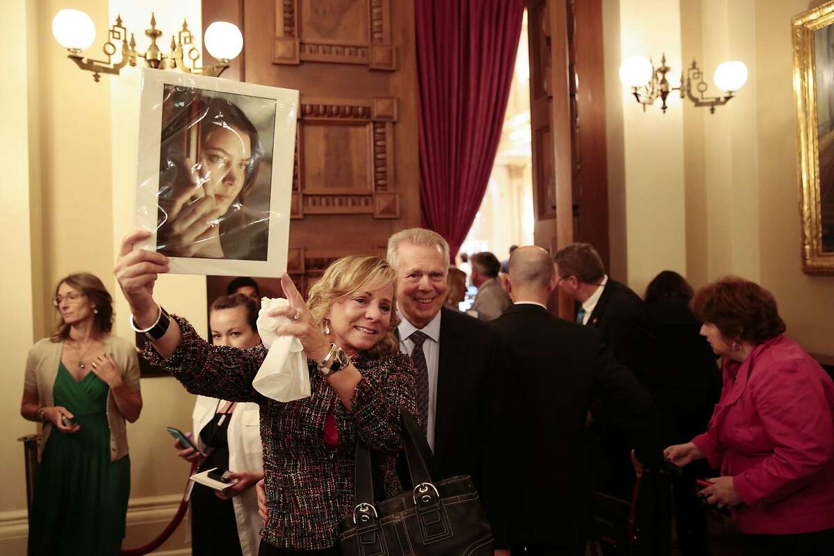 Debbie Ziegler holds a picture of her late daughter, Brittany Maynard, who moved to Oregon after receiving a diagnosis of terminal cancer so she could end her life on her own terms, with Gary Holme, her husband, after hearing the End of Life Option Act was passed at the California State Capitol in Sacramento, Sept. 11, 2015. In a landmark victory for supporters of assisted suicide, the California State Legislature on Friday approved a bill that would allow doctors to help terminally ill people end their own lives. California Gov. Jerry Brown signed the