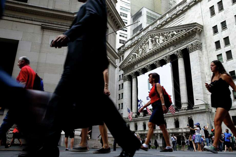 Pedestrians pass by the New York Stock Exchange. Thanks largely to a big jump on Tuesday, the stock market finished with a 2 percent gain for the week. Photo: Seth Wenig, STF / AP