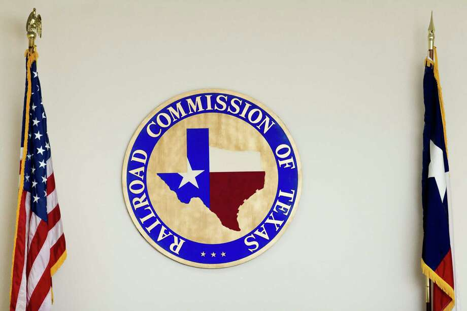 Flags frame the logo of the Texas Railroad Commission, which regulates oil and gas activities in the state, at its headquarters in Austin.  (Christina Burke/ for Houston Chronicle) Photo: Christina Burke, Freelance / Christina Burke
