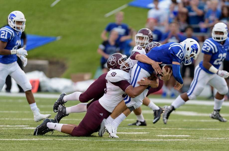 Cy Fair 14, Cy Creek 7  Luke Allen (15) of the Cy Creek Cougars is brought down by Greg Linton (35) of the Cy Fair Bobcats after a short gain in the first half on Friday, September 11, 2015 at Pridgeon Stadium. Photo: Wilf Thorne, For The Chronicle