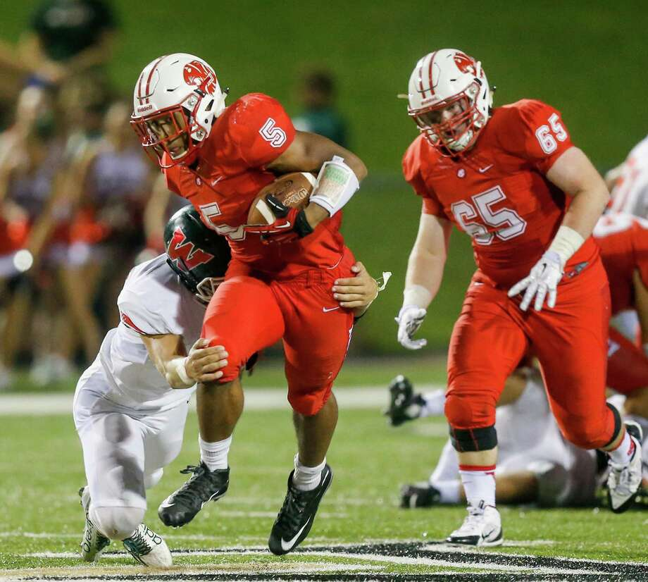 Katy running back Kyle Porter (5) fends off a tackle from defensive back David Lee (33) for a gain. Porter scored the only touchdowns for Katy. Photo: Bob Levey, Photographer / ©2015 Bob Levey