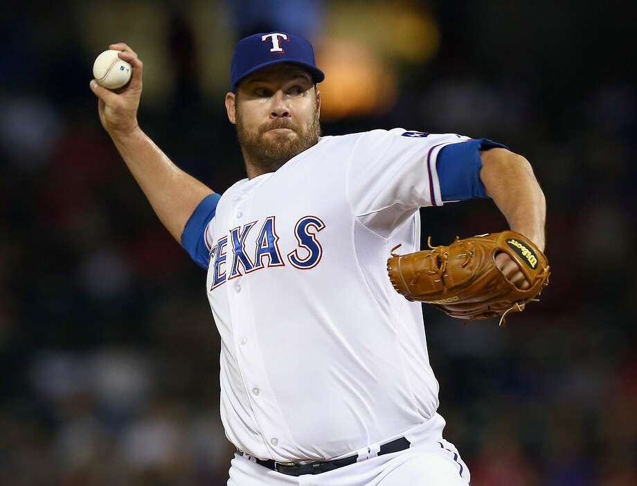 Colby Lewis, perfect through seven innings, finished with a two-hitter against the A's. Photo: Tom Pennington, Getty Images