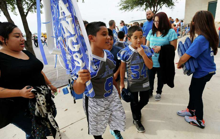 Josiah Flores, 9, carries a spirit stick as he and other young fans from his youth football league head into Gustafson Stadium to watch Jay against Del Rio on Friday, Sept. 11, 2015. (Kin Man Hui/San Antonio Express-News) Photo: Kin Man Hui, Staff / San Antonio Express-News / ©2015 San Antonio Express-News
