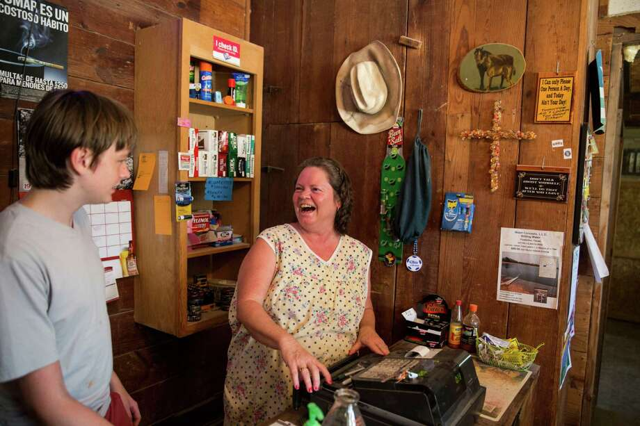 Joy Tipton and her son, Evan Tipton, share a joke at the family's roadside store, the Little White House, in Fowlerton. The store is along the highway between Tipton and Cotulla and mainly serves hunters and oil field workers. Photo: Carolyn Van Houten, Staff / San Antonio Express-News