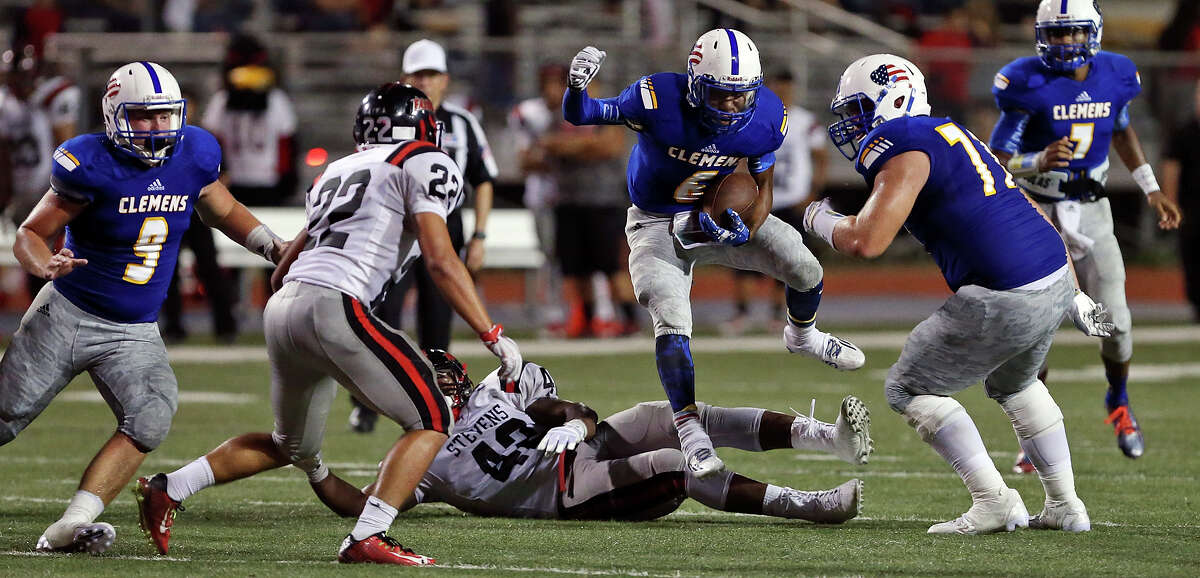 Clemens' Marshawn Brown (center) leaps over Stevens' Elijah Earls as during second half action Friday Sept. 11, 2015 at Lehnhoff Stadium. Clemens won 56-21.