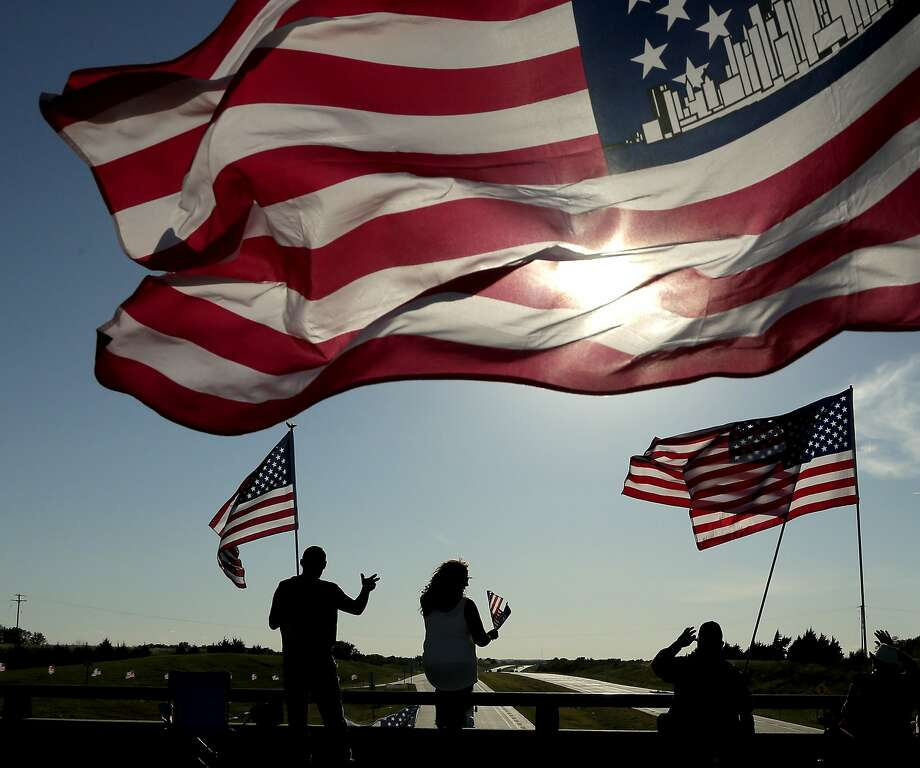 People wave at passing motorists from an overpass over Interstate 35 near Pomona, Kan., Friday, Sept. 11, 2015, in commemoration of the 14th anniversary of the 9/11 terror attacks. Residents annually mark the attacks from the bridge by waving flags from sunrise to sunset.  Photo: Charlie Riedel, Associated Press