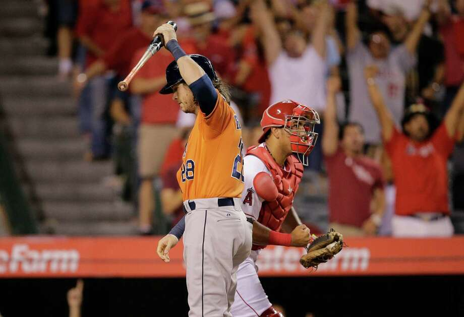 Houston Astros' Colby Rasmus, left, reacts after striking out as Los Angeles Angels catcher Carlos Perez pumps his fist celebrating his team's 3-2 win. Photo: Jae C. Hong, STF / AP