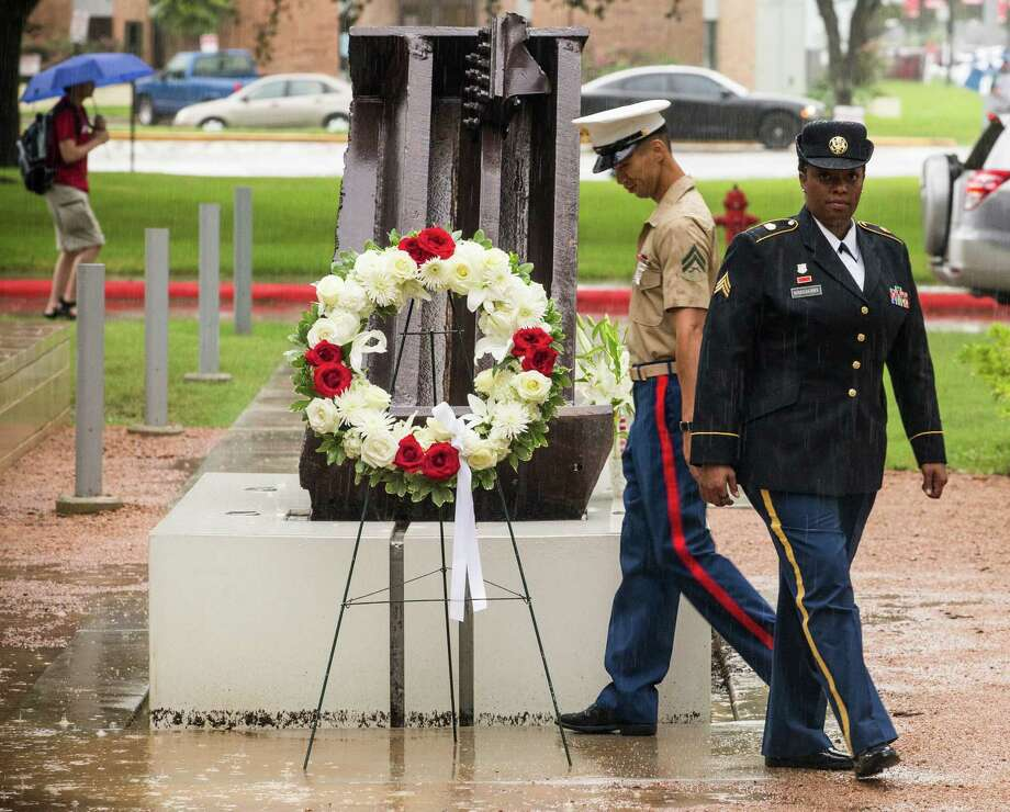 "Cpl. Phan Tan, left, and Sgt. Lawren Bradberry lay a wreath next to a section of the World Trade Center during a ""Remembering 9/11"" ceremony at the University of Houston on Friday, Sept. 11, 2015, in Houston. Photo: Brett Coomer, Houston Chronicle / © 2015 Houston Chronicle"