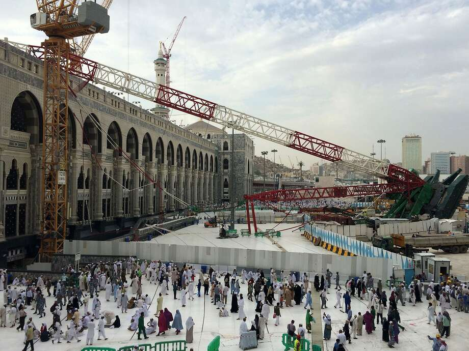 Muslim pilgrims walk past the crane that collapsed at the Grand Mosque in the holy city of Mecca. More than 100 people were killed when the crane fell during a violent storm. Photo: Ahmed Farwan, AFP / Getty Images