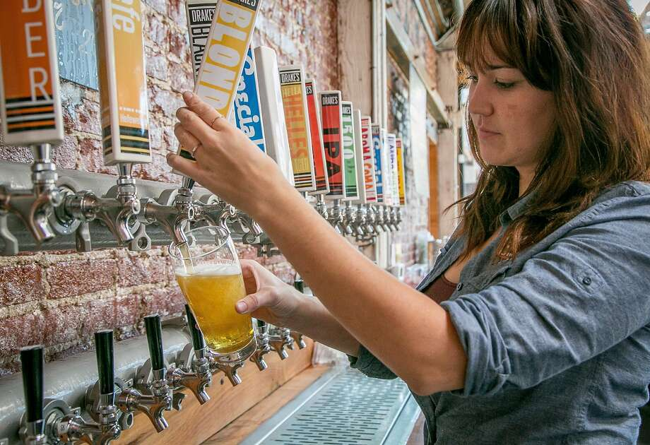Teresa Whisenhunt pours a beer at Drake's Dealership in Oakland. Photo: John Storey, Special To The Chronicle