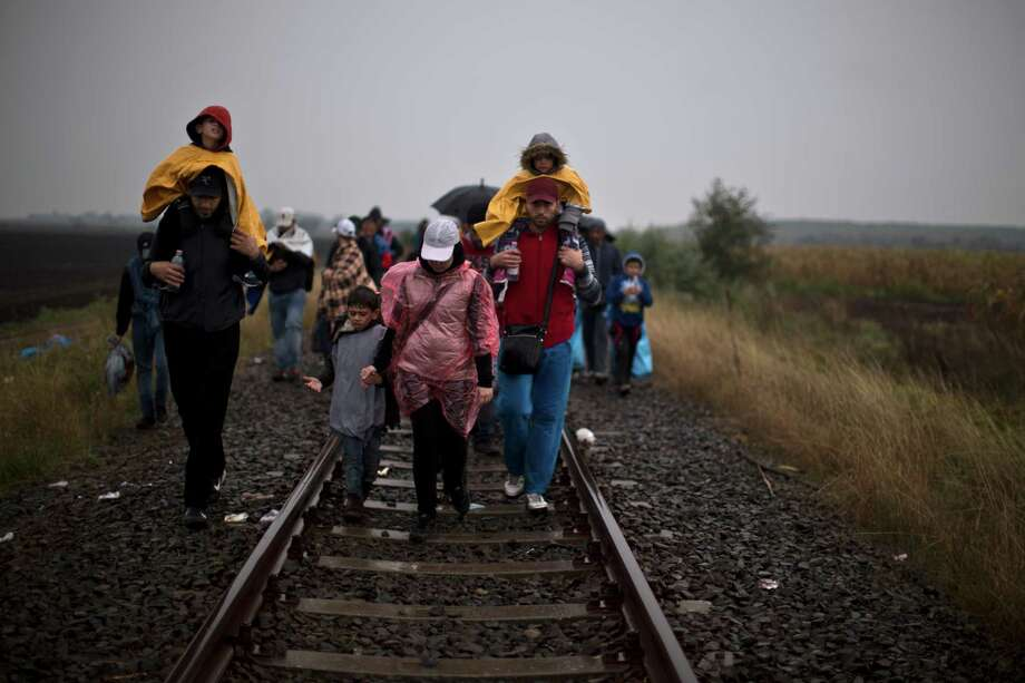 Syrian refugees walk on a railway track in Roszke, southern Hungary. Photo: Muhammed Muheisen, STF / AP