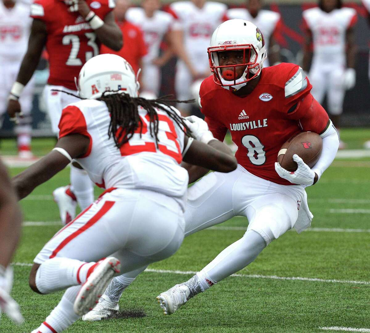 Louisville quarterback Lamar Gackson (8) attempts to run the ball past the defense of Houston's Trevon Stewart (23) during the second half of an NCAA college football game in Louisville, Ky. Saturday, Sept. 12, 2015. Houston defeated Louisville 34-31. (AP Photo/Timothy D. Easley)