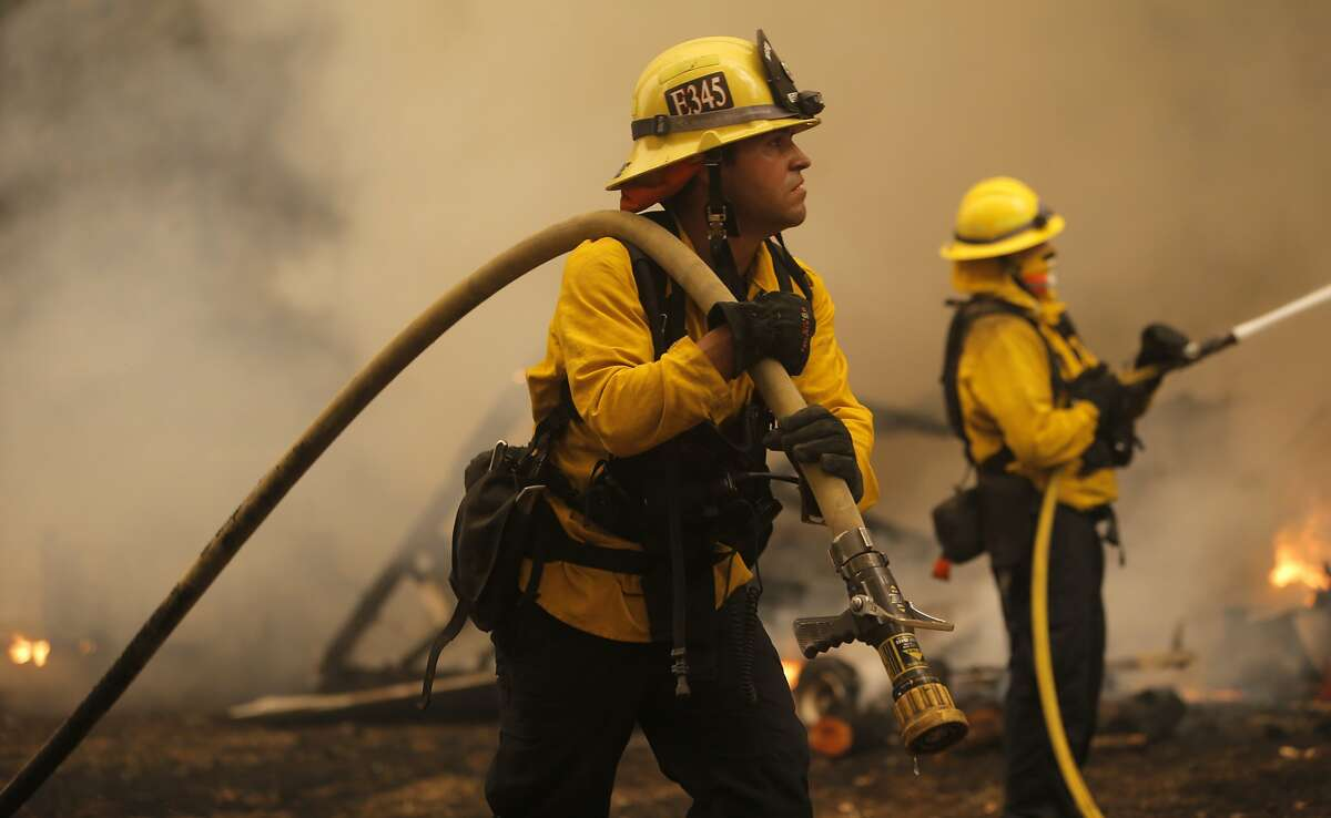 Firefighter Jarrett LaShure from Ventura Co. works to extinguish an out building along Sheep Ranch Road in Sheep Ranch, Calif, as the Butte Fire continues to burn on Sat. September 12, 2015.