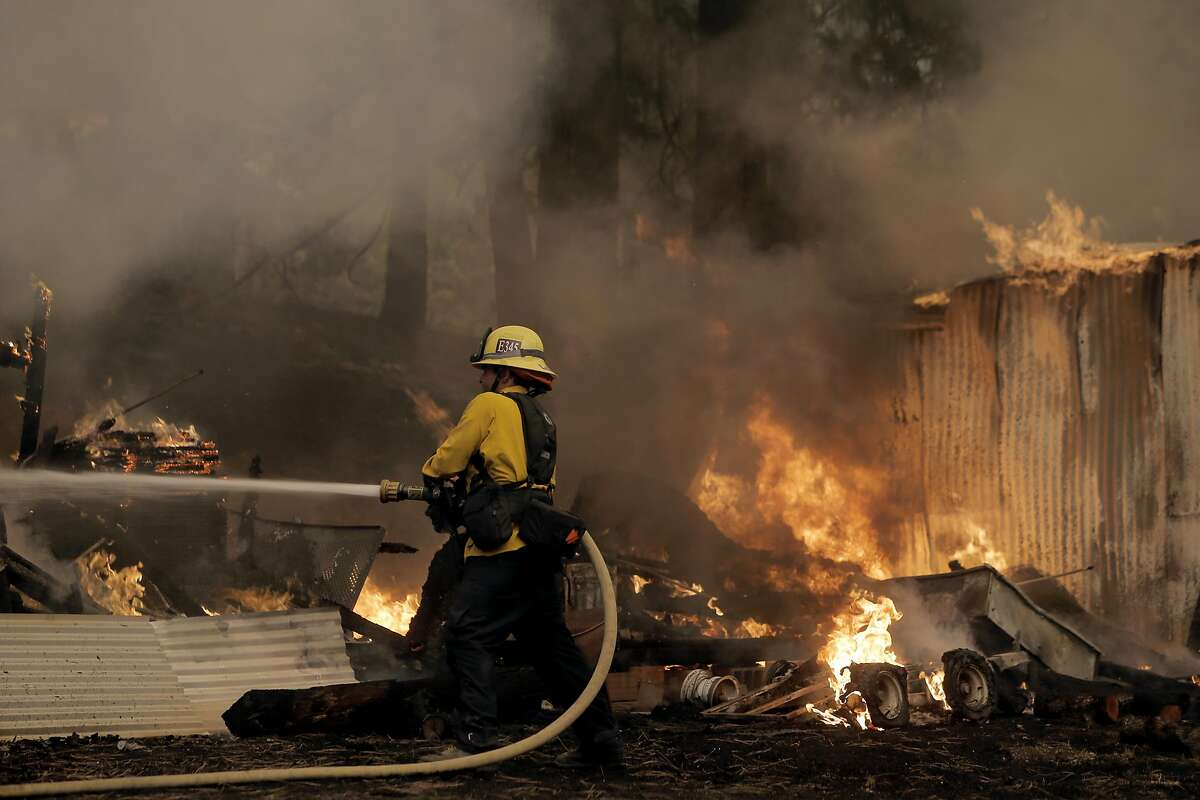 Firefighter Jarrett LaShure from Ventura Co. extinguishes an out building along Sheep Ranch Road in Sheep Ranch, Calif, as the Butte Fire continues to burn on Sat. September 12, 2015.