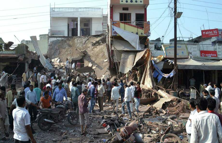 A crowd gathers Saturday at the site of an explosion in Petlawad, in the central Indian state of Madhya Pradesh, where dozens of people were killed at a restaurant when a cooking gas cylinder exploded. The blast triggered a second explosion of mine detonators stored illegally nearby, police said. Photo: Manoj Jani, STR / AP