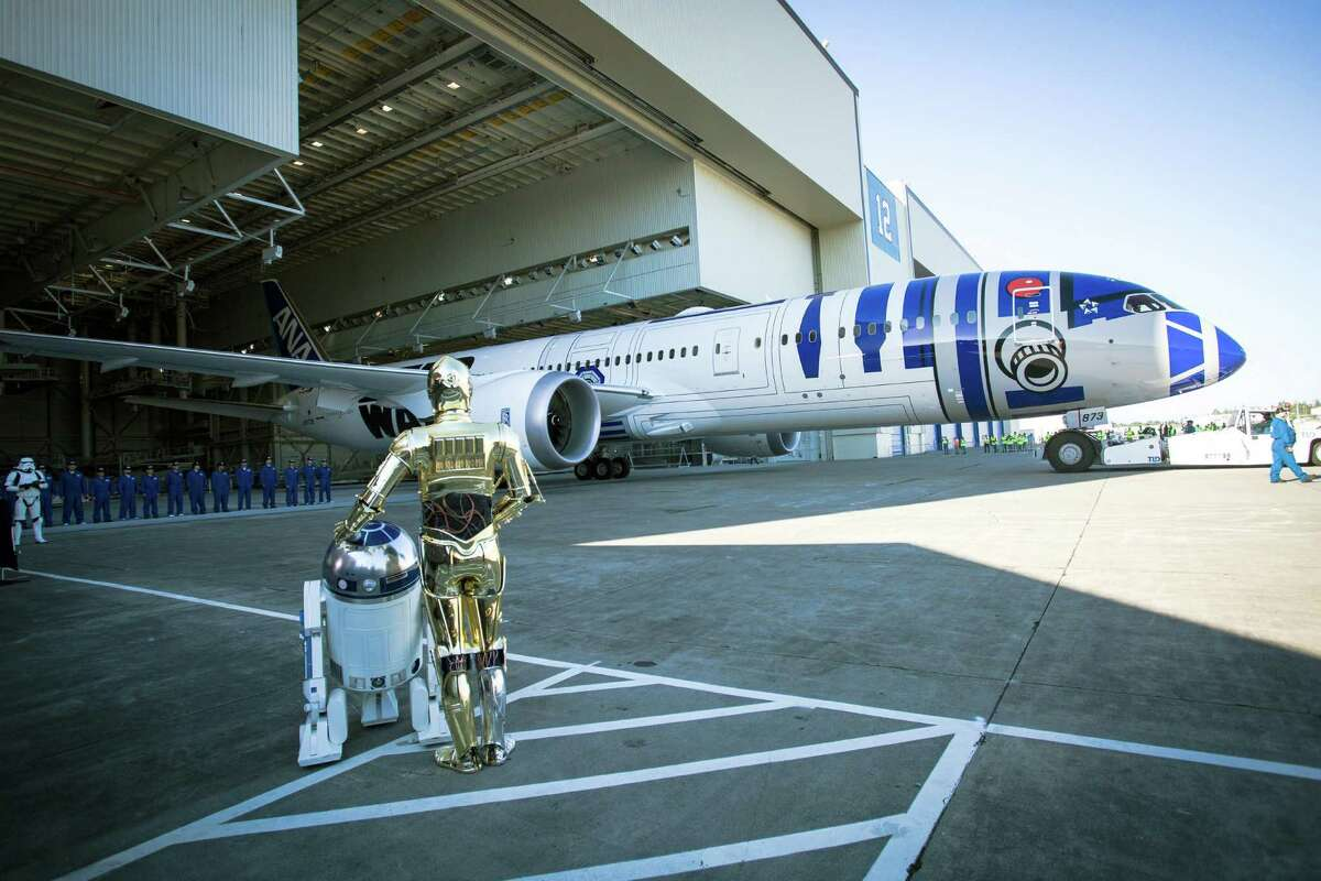 R2-D2 and C3-PO watch as the R2-D2-themed Boeing 787-9 Dreamliner rolls out of a hangar at Boeing field in Everett on Saturday, September 12, 2015. Boeing and ANA revealed their collaboration with the Walt Disney Company (Japan) for the ANA Jet that will begin long range service in October.