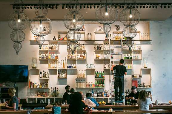 The bar at Calavera in Oakland displays many shelves full of different bottles of mezcal.