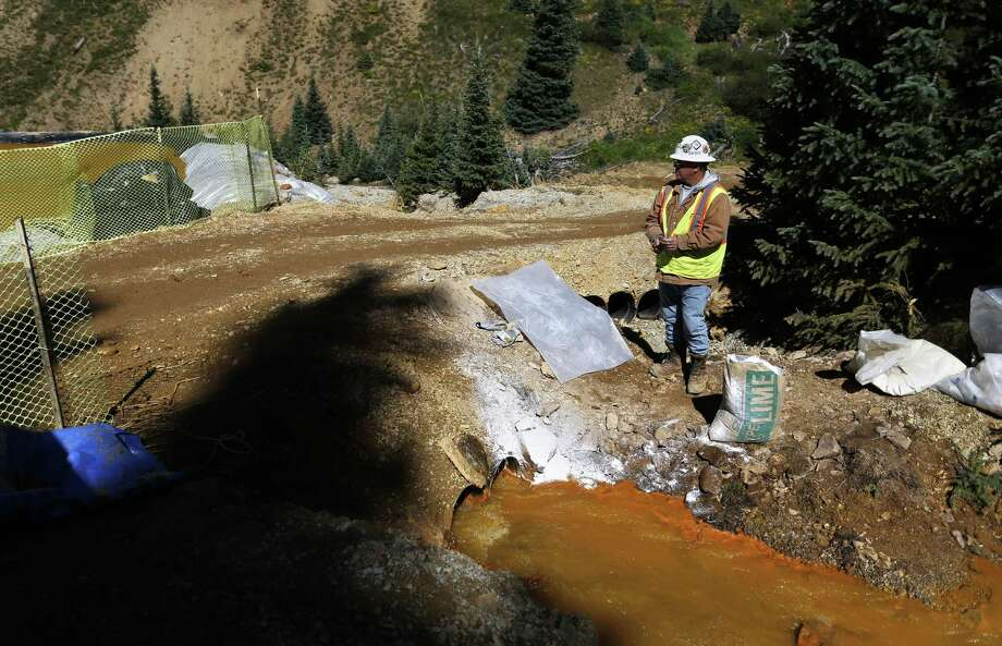 FILE - In this Aug. 14, 2015 file photo, an Environmental Protection Agency contractor keeps a bag of lime on hand to correct the PH of mine wastewater flowing into a series of sediment retention ponds, part of danger mitigation in the aftermath of the blowout at the site of the Gold King Mine, outside Silverton, Colo. Federal officials say they have suspended cleanup work and investigations covering 10 mining sites in four states to guard against a repeat of last month's massive wastewater spill from an inactive Colorado gold mine. Details provided to The Associated Press show the order applies to three sites in California, four in Colorado, two in Montana and one in Missouri. (AP Photo/Brennan Linsley, file) Photo: Brennan Linsley, STF / AP