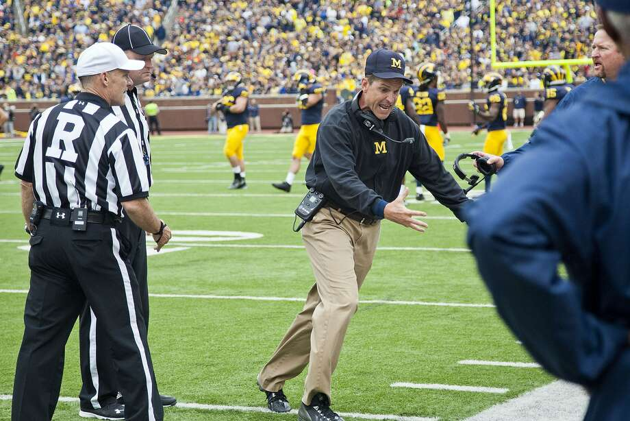 Michigan head coach Jim Harbaugh pleads his case with officials after his team was called for a penalty on a punt. The infraction wiped out a change of possession in the second quarter. Photo: Tony Ding, Associated Press