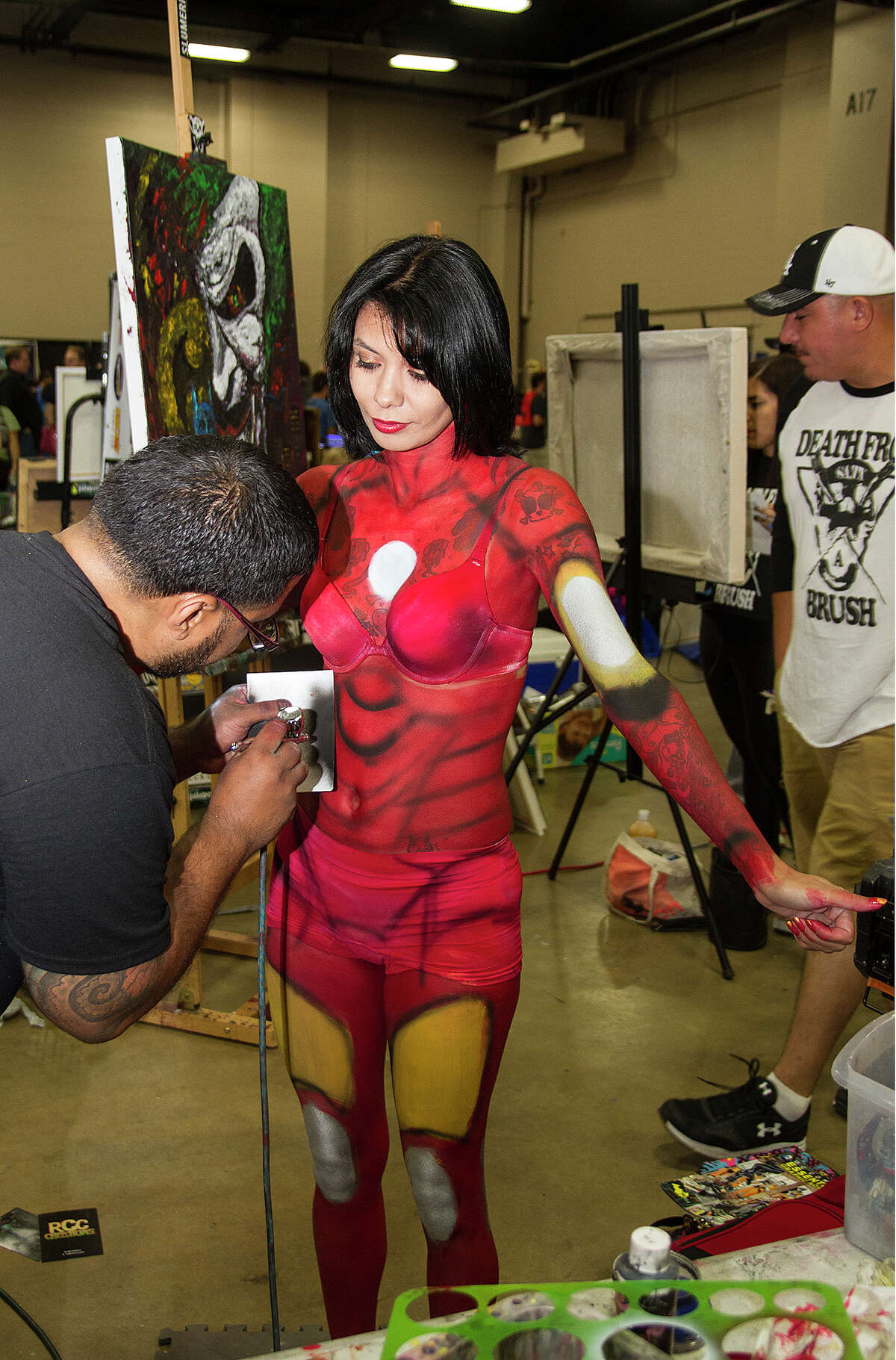 Jason Garcia spray paints Jennifer Badillo at the Death From Brush booth, Saturday, Sept. 12, 2015 at Alamo City Comic Con at the Henry B. Gonzalez Convention Center.