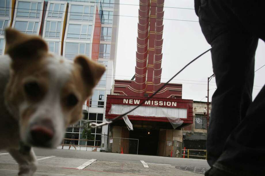 The New Mission Theater, located next to the new Vida condo project (left of frame), is behind a dog and pedestrian walking on Mission Street between 21st  and 22nd Streets on Monday, June 22, 2015. Photo: Lea Suzuki / The Chronicle / ONLINE_YES