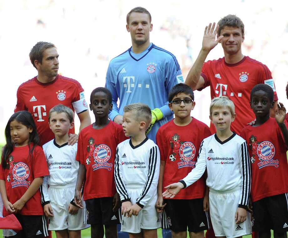 Back row from left: Munich players Philipp Lahm, goal keeper Manuel Neuer and Thomas Mueller pose  with migrant and  refugee children  before the German Bundesliga soccer match between FC  Bayern Munich and FC Augsburg at the Allianz Arena in Munich, Germany, Saturday Sept. 12, 2015. (Andreas Gebert/dpa via AP) Photo: Andreas Gebert, SUB / dpa