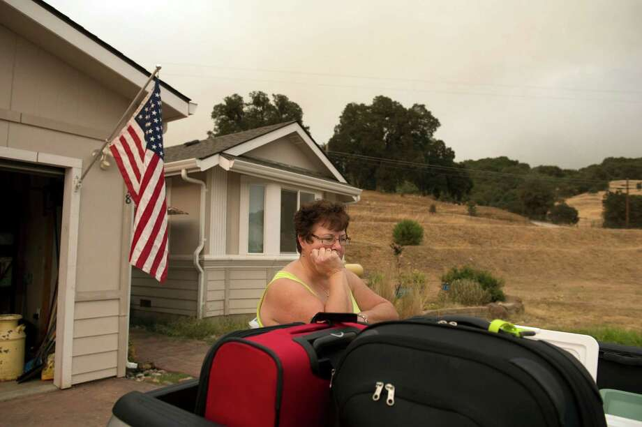 Ready to evacuate, Teri Goodall waits outside her home in San Andreas as the Butte Fire burns out of control north of San Andreas, Calif. on Friday, Sept. 11, 2015. (Jose Luis Villegas/The Sacramento Bee via AP) Photo: Jose Luis Villegas, MBI / Associated Press / The Sacramento Bee