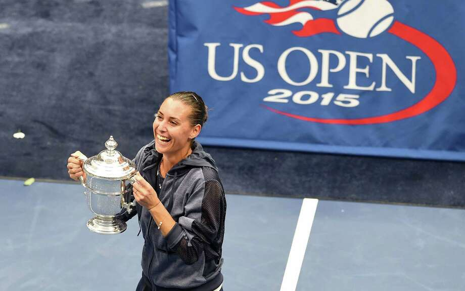Flavia Pennetta of Italy celebrates with her winning trophy after defeating her compatriot Roberta Vinci during their 2015 US Open Women's singles final match at the USTA Billie Jean King National Tennis Center in New York on September 12, 2015. Pennetta won her first Grand Slam singles title defeating Vinci 7-6 (7/4), 6-2 in the US Open women's final, then promptly retired. AFP PHOTO/JEWEL SAMADJEWEL SAMAD/AFP/Getty Images ORG XMIT: 571788285 Photo: JEWEL SAMAD / AFP