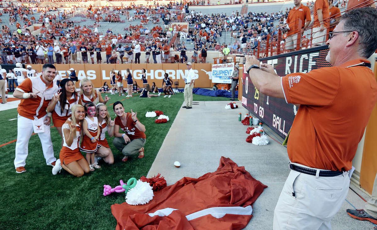 Scott Willingham, Vice President & General Manager Longhorn IMG Sports Marketing, (right) photographs Jennifer S. Mueller, HEB Senior Marketing Manager, and her daughter Remi Mueller, 4, with Texas Longhorns Cheerleaders before the Texas and Rice football game at Texas Memorial Stadium Saturday Sept. 12, 2015 in Austin, Tx.