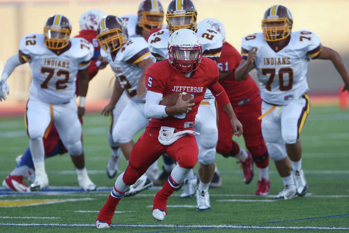 Jesse Flores of Jefferson runs from the Harlandale defense during high school football action at Alamo Stadium on Saturday, Sept. 12, 2015.