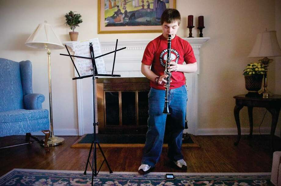 Joe Lupinacci, 13,  practices his clarinet in his living room in Stamford, Conn. on Friday, March 19, 2010.   With funding eliminated for the city's Project Music, Joe, a seventh grader at Rippowam Middle School, will no longer be to take clarinet lessons. Photo: Kathleen O'Rourke / Stamford Advocate