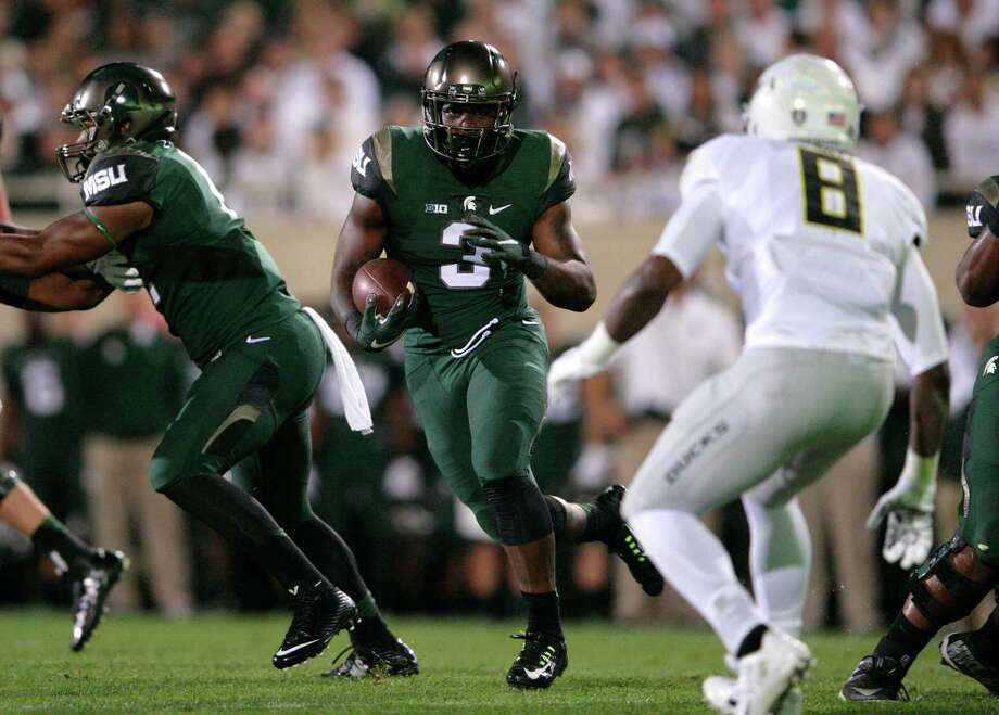 Michigan State's L.J. Scott (3) rushes against Oregon's Reggie Daniels (8) as Michigan State's Jamal Lyles, left, blocks during the first quarter of an NCAA college football game, Saturday, Sept. 12, 2015, in East Lansing, Mich. (AP Photo/Al Goldis) ORG XMIT: ELJ112 Photo: Al Goldis / FR11125 AP
