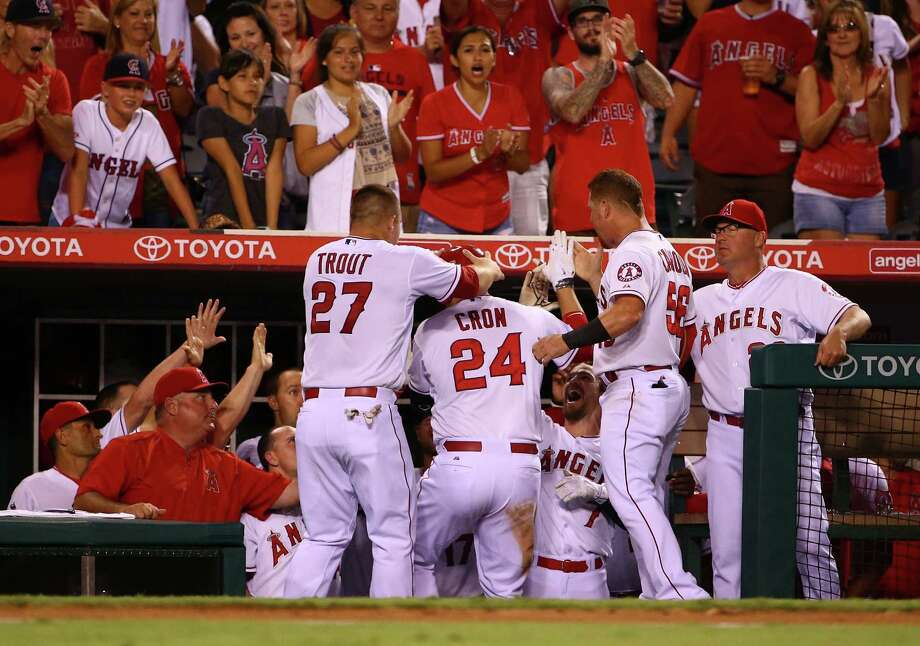 The Angels mob C.J. Cron after his tiebreaking homer in the eighth inning Saturday night. Photo: Victor Decolongon, Stringer / 2015 Getty Images