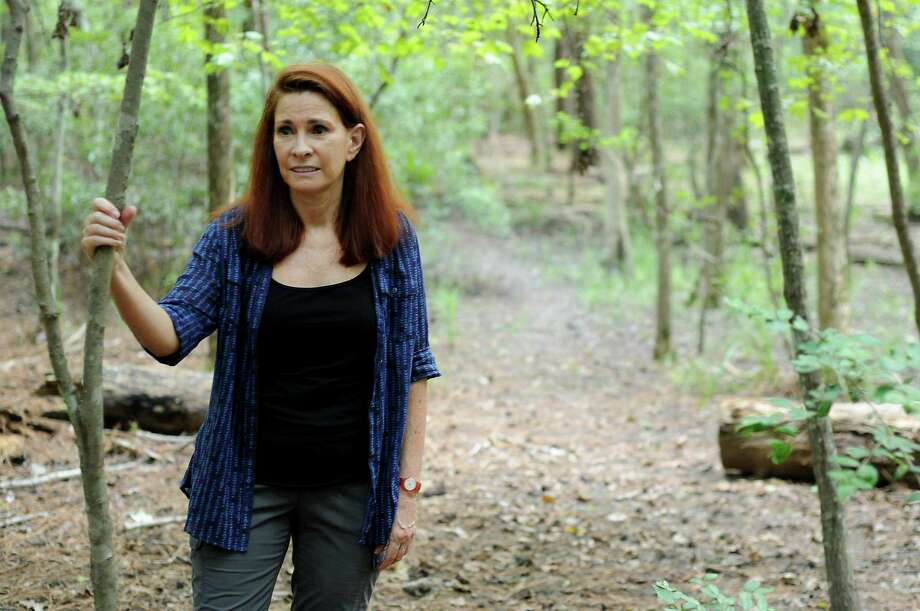 "Linda Estrada, in the woods behind her home in the Woodlands. She's glad coyotes have returned to her neighborhood. ""They do good for nature, and they're supposed to be there."" Photo: Dave Rossman, For The Chronicle / Freelalnce"