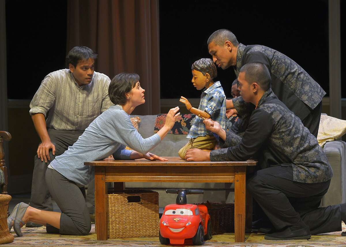 """Father (Kurt Uy, left) and Mother (Christine Albright) with their son, identified as the Oldest Boy (played by Tsering Dorjee (Bawa), upper right, and the puppet Tenzin with puppeteers Jed Parsario, almost hidden and Melvign Badiola) in Marin Theatre Company's """"The Oldest Boy"""""""