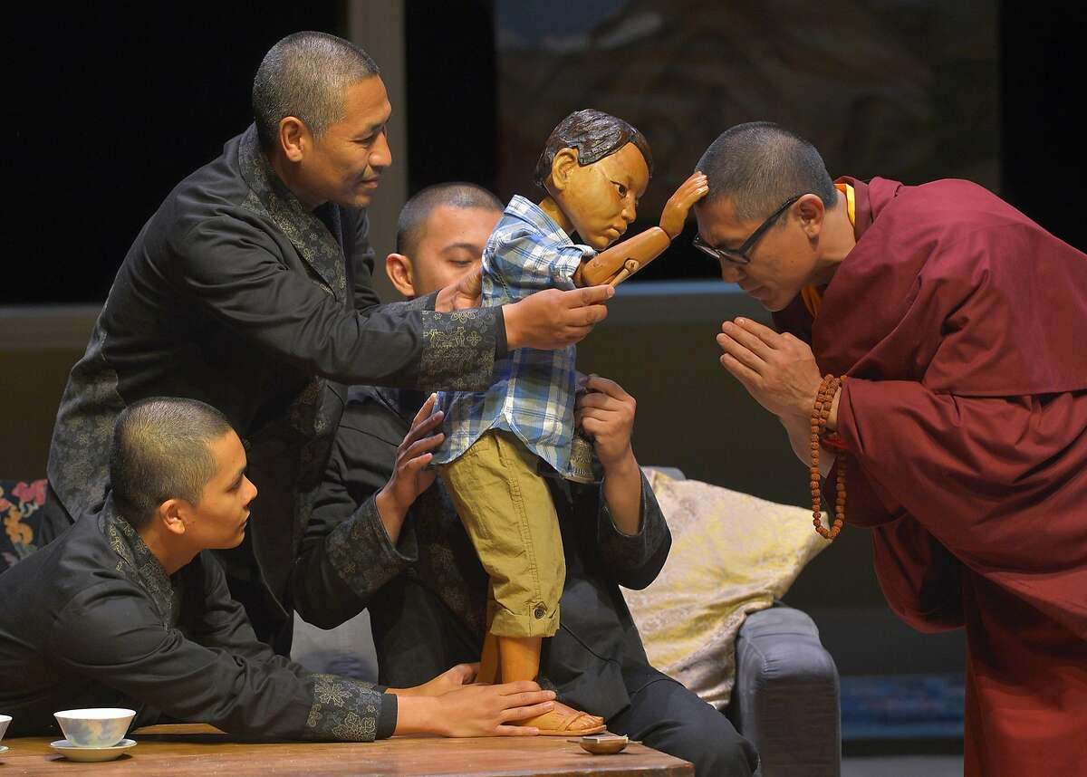 """Lama (Jimm S. Kim, right) is blessed by the Oldest Boy (played by Tsering Dorjee (Bawa), upper left, and, in child form, the puppet Tenzin with puppeteers Jed Parsario, lower left and Melvign Badiola) in Marin Theatre Company's """"The Oldest Boy"""""""