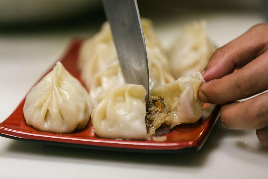 A dumpling is sliced open to reveal its lamb filling in the kitchen at Uyghur Taamliri, a pop-up that serves Uighur food — the cuisine of the Muslims of northwest China — at the Chug Pub in S.F. Photo: Jen Fedrizzi, Special To The Chronicle