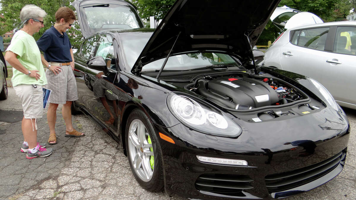 Denise Howard and J.E. Martin check out the 2015 Porsche Panamera S E-Hybrid, which has a starting sticker price of $106,100, at Fairfield's First Electric Vehicle Showcase on Saturday.
