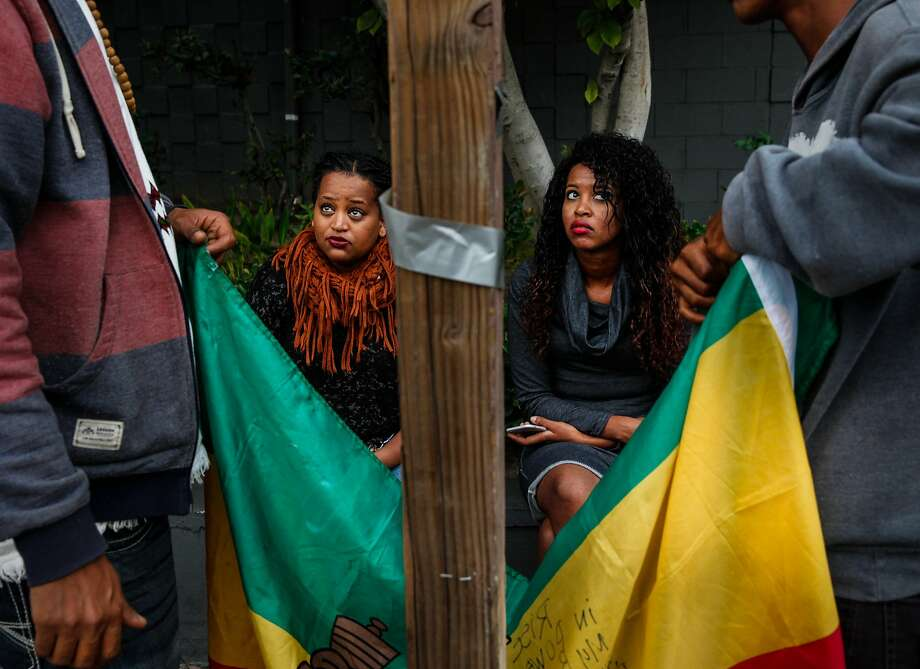 Mourners watch as an Ethiopian flag is hung on a telephone poll in Oakland at a vigil for Yonas Alehegne, a refugee who suffered mental illness and spent time at San Quentin before being fatally shot by police. Photo: Sarah Rice, Special To The Chronicle