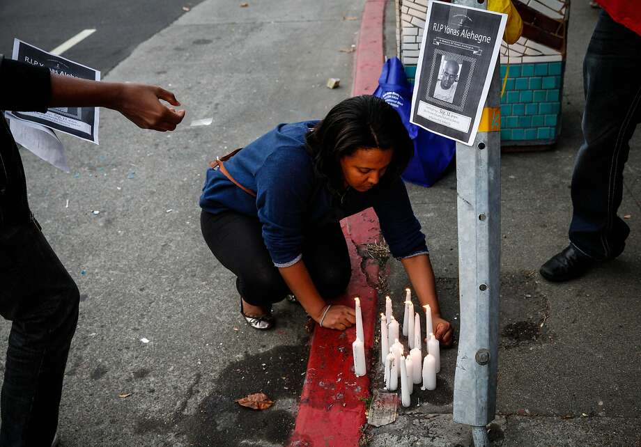Elizabeth Tena lights candles at a vigil for Yonas Alehegne, an Ethiopian immigrant who was shot and killed by an Oakland police officer in August, in Oakland, Calif., on Sunday, September 13, 2015. Photo: Sarah Rice, Special To The Chronicle