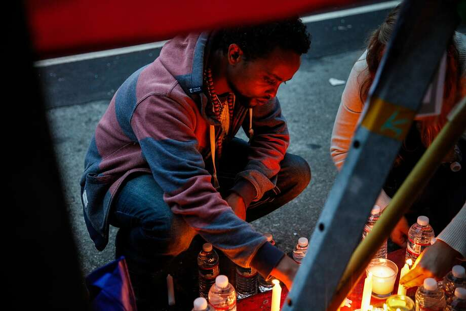 Fikre Atnafe lights candles at a vigil for Yonas Alehegne, an Ethiopian immigrant he knew who was shot and killed by an Oakland police officer in August, in Oakland, Calif., on Sunday, September 13, 2015. Photo: Sarah Rice, Special To The Chronicle