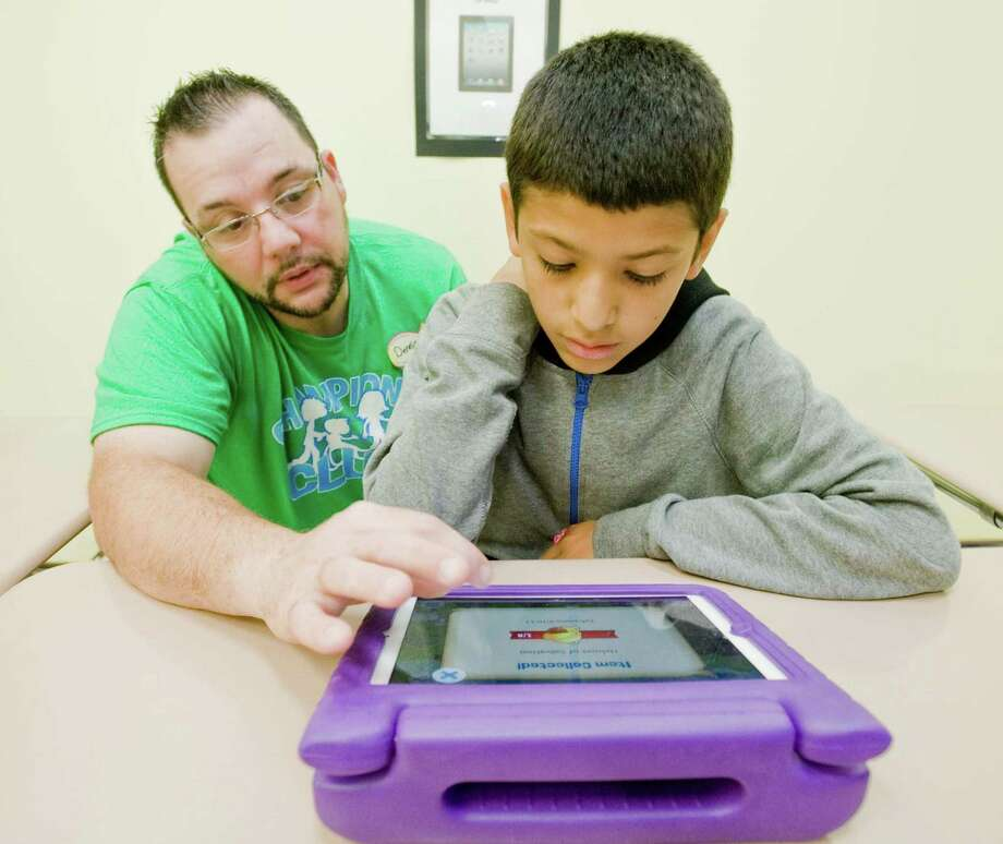 The Champions Club Support Provider Dennis Martello helps Jonathan Ortiz, 11 of Waterbury, with a bible app at the Club inside Faith Church in New Milford. Sunday, Sept. 13, 2015 Photo: Scott Mullin / For The / The News-Times Freelance
