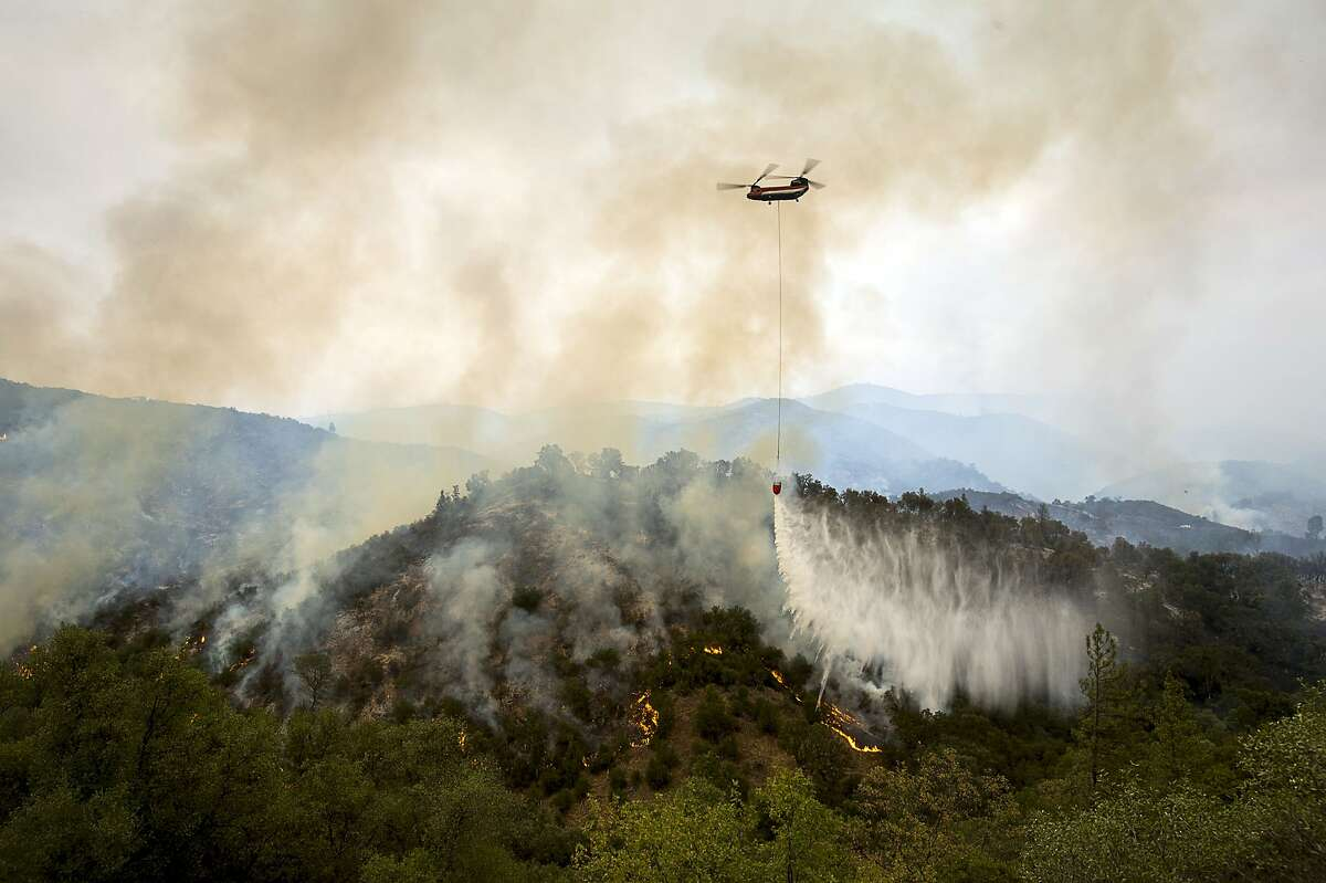Helicopter drops water on hillside of Murray Creek Road during the Butte Fire on Saturday, Sept. 12, 2015, in San Andreas, Calif. The Butte fire started Wednesday east of the Amador County town of Jackson and is forcing evacuations in the dry hills east of Highway 49.
