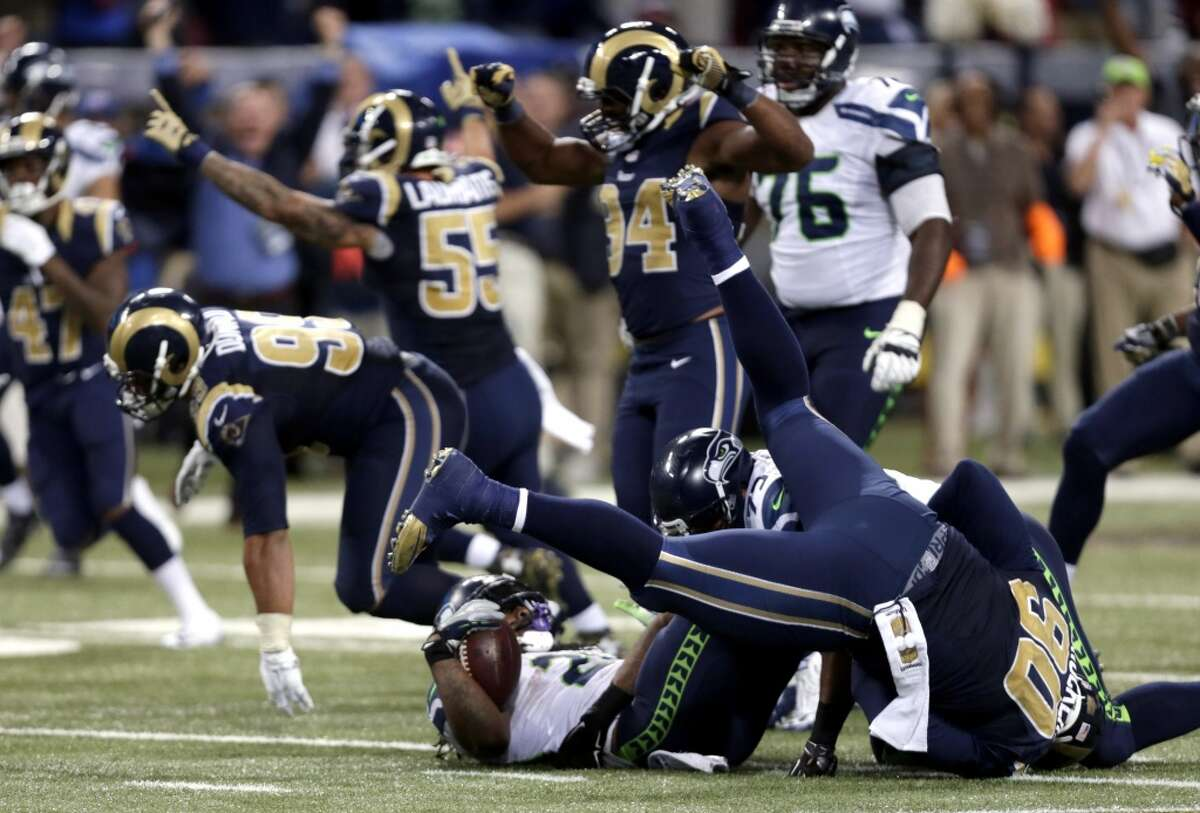 Seattle Seahawks running back Marshawn Lynch lands on his back as he is stopped on fourth down and St. Louis Rams players celebrate on the final play in overtime of an NFL football game Sunday, Sept. 13, 2015, in St. Louis. The Rams won 34-31. (AP Photo/Tom Gannam)