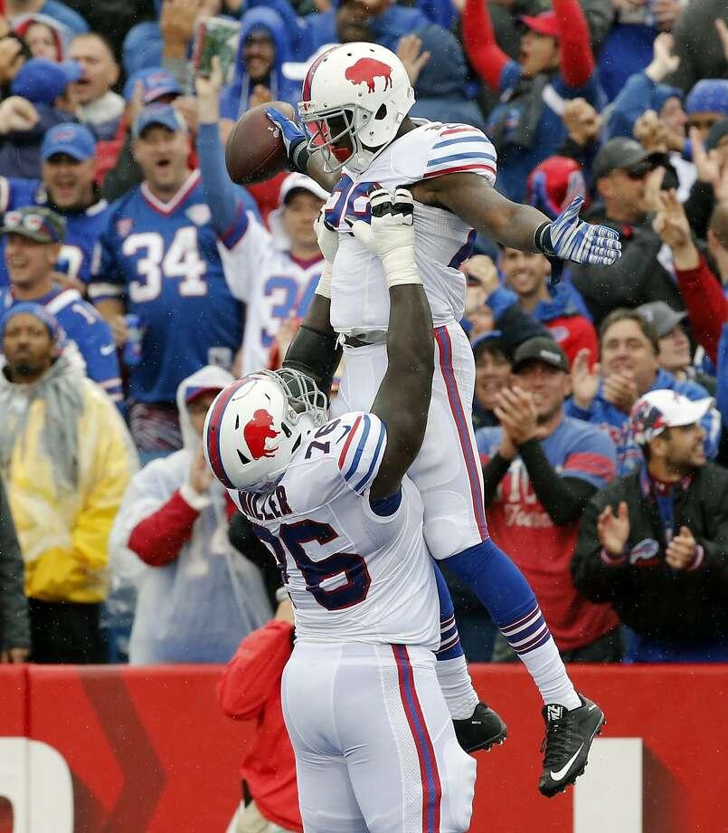 Bills running back Karlos Williams (right) is held up by teammate John Miller after scoring a TD. Photo: Bill Wippert, Associated Press