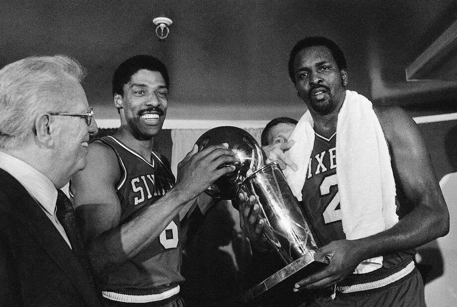 FILE - In this Tuesday, May 31, 1983 file photo, Philadelphia 76ers Julius Erving, left, and Moses Malone, right, hold the NBA Championship trophy after defeating the Los Angeles Lakers in  Los Angeles. Malone, a three-time NBA MVP and one of basketball's most ferocious rebounders, died Sunday, Sept. 13, 2015, according to a The Philadelphia 76ers statement. He was 60. (AP Photo/File) Photo: Associated Press
