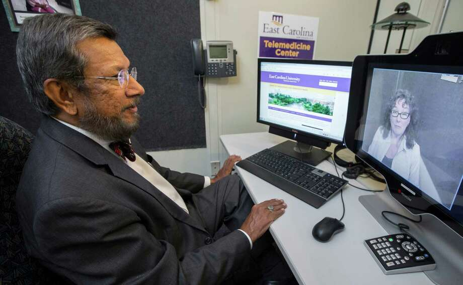 """Dr. Sy Saeed, chair of psychiatry and behavioral medicine at the Brody School of Medicine at East Carolina University, speaks to a colleague, Clinical Telehealth Manager Gloria Jones, during a routine test of the telepsychiatry system in Greenville, N.C. Saeed says it usually takes only a few moments for a new patient to feel at ease with the two-way video technology. """"It's the same for psychiatrists,"""" he said. Photo: East Carolina University / East Carolina University"""