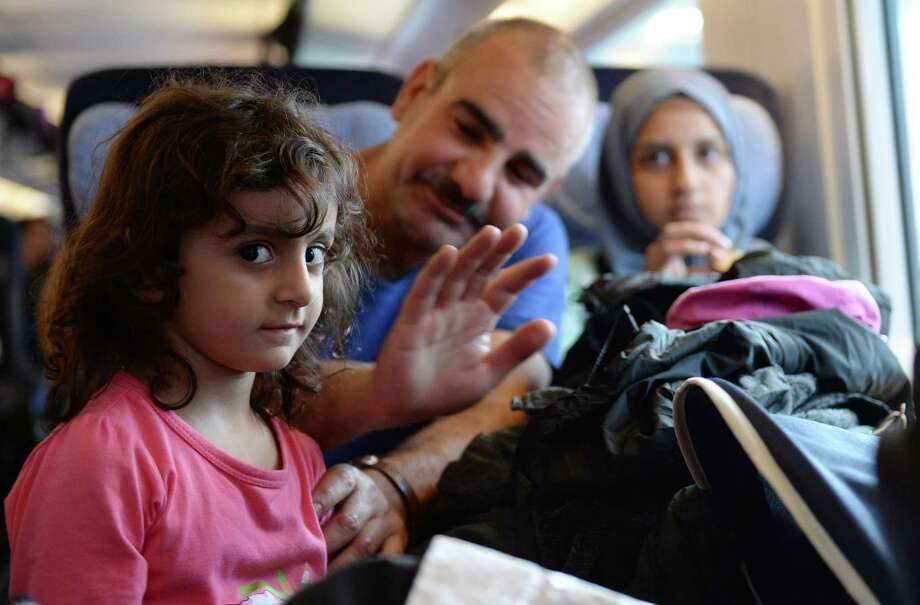 A migrant family from Syria sits in a special train at the train station in Munich, southern Germany, on September 13, 2015. Thousands of refugees arrived in Germany during the weekend, coming from Hungary and Austria. AFP PHOTO / CHRISTOF STACHECHRISTOF STACHE/AFP/Getty Images Photo: CHRISTOF STACHE, Stringer / AFP / Getty Images / CHRISTOF STACHE