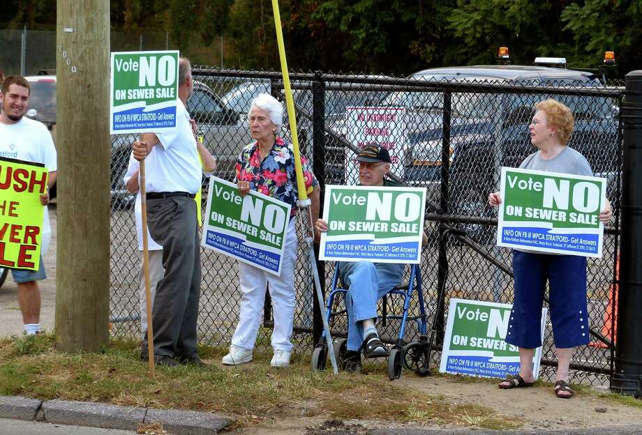 Protesters against the sale of the Stratford sewage treatment plant to the Greater New Haven Water Pollution Control stand at the entrance to Two Roads Brewery in Stratford, Conn., on Wednesday Sept. 9, 2015. Many proponents of the sale held a fundraiser for Mayor John Harkins inside the brewery, ahead of the referendum set for Nov. 3. Photo: Christian Abraham / Hearst Connecticut Media / Connecticut Post